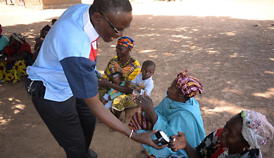 Abdoulaye Traoré, der die Fabrik in sein Dorf gebracht hat und in der Gegend gut bekannt ist, lässt die Frauen Malibelle probieren, die gute Creme mit Karitébutter aus Siokoro.