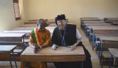 Der Bezirksbürgermeister und Gunthard Weber gemeinsam auf einer Schulbank.