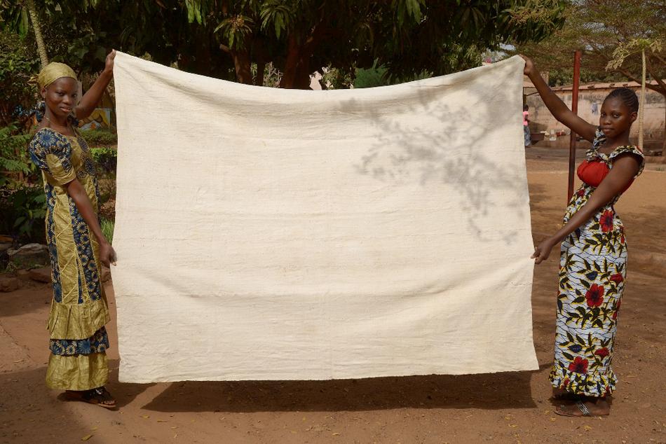 Schneiderinnen mit fertiger Decke aus handgesponnener Baumwolle.