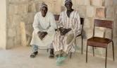 Zwei Dorfälteste in Raum der Frauenkooperative, die der Besprechung  von Tapily und mir zusehen.