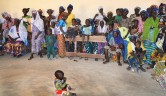120 begeisterte Frauen der Frauenkooperative, die von der Förderung ihrer Projekte erfahren in Klassenzimmer der Grundschule.