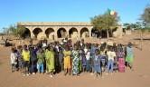 Schulkinder vor dem einen der beiden von HdH finanzierten Schulgebäude mit malischer Flagge.